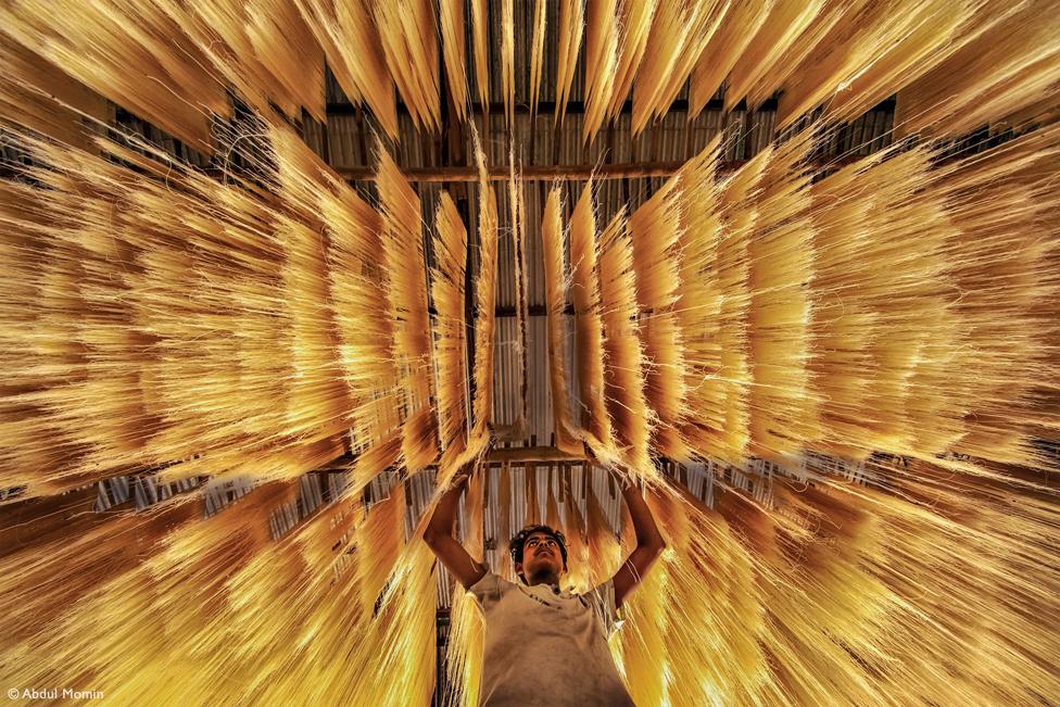 Un hombre con unos fideos de arroz que cuelgan sobre él