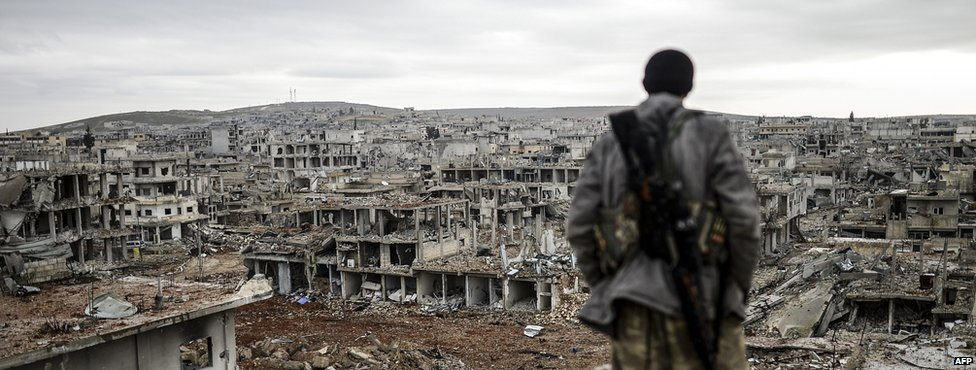 Musa, a 25-year-old Kurdish marksman, stands atop a building as he looks at the destroyed Syrian town of Kobane, also known as Ain al-Arab or Kobani, on January 30, 2015.