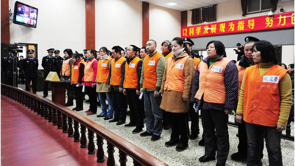 A group of accused members of a child trafficking ring stand before a court in Wuhan, central China's Hubei province on 3 March 2010.