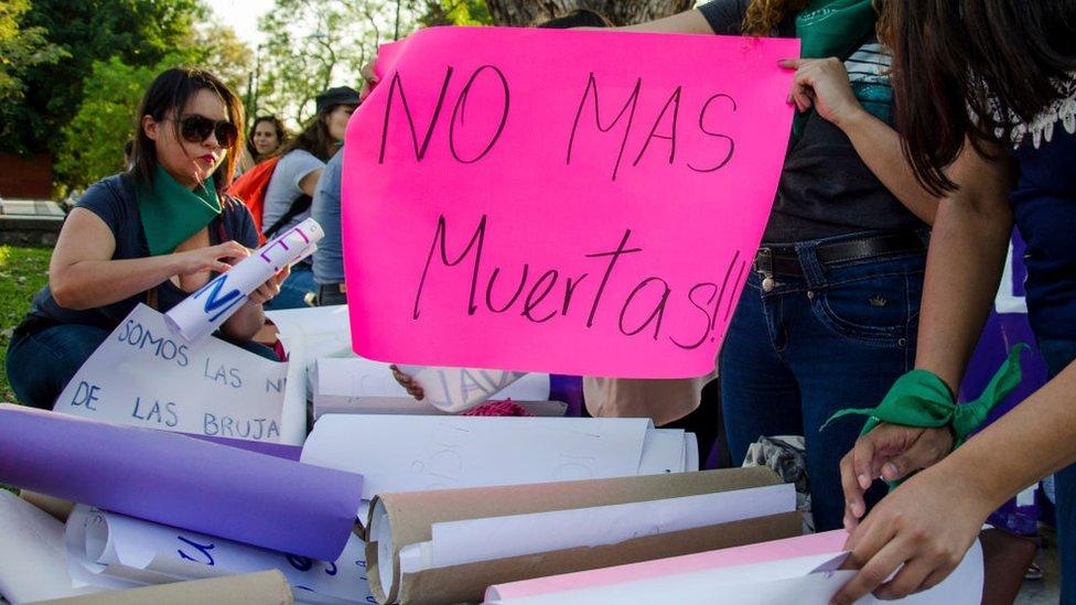 """Mujeres en una protesta con un cartel que dice """"No más muertas""""."""