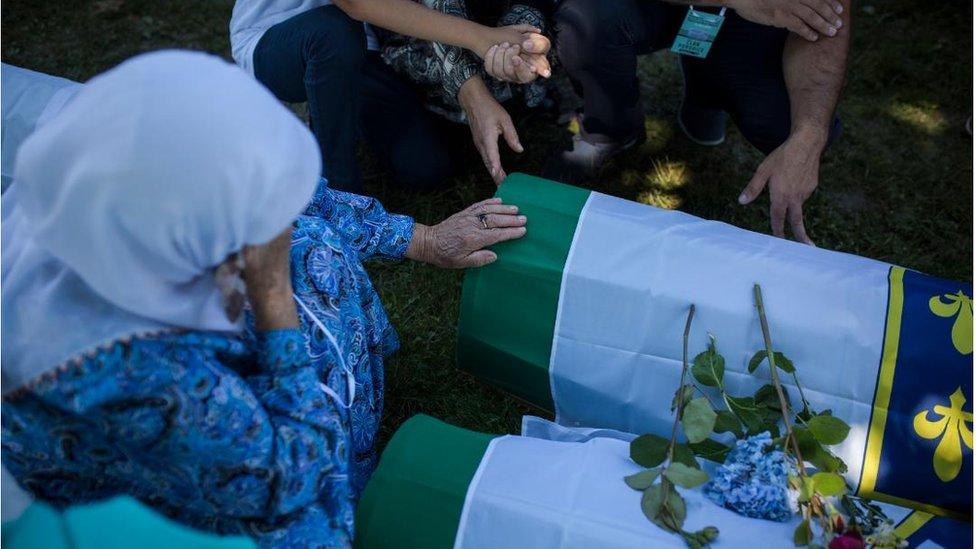 Žena drži glavu u rukama pored tabuta, Potočari 2018