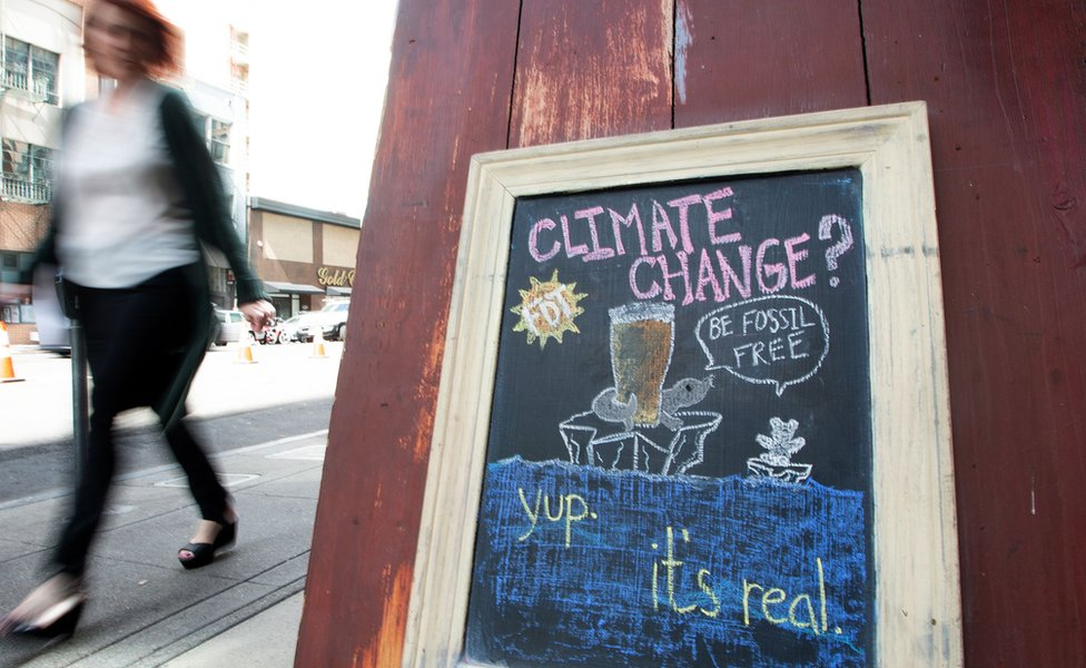 A woman walks by a sign about climate change in front of a bar in downtown San Francisco. September 2018