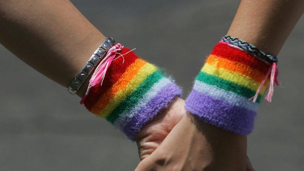 Women wearing rainbow wristbands hold hands