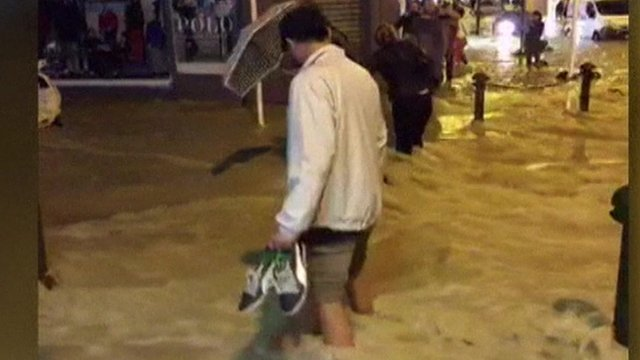 Man holding shoes wading through water