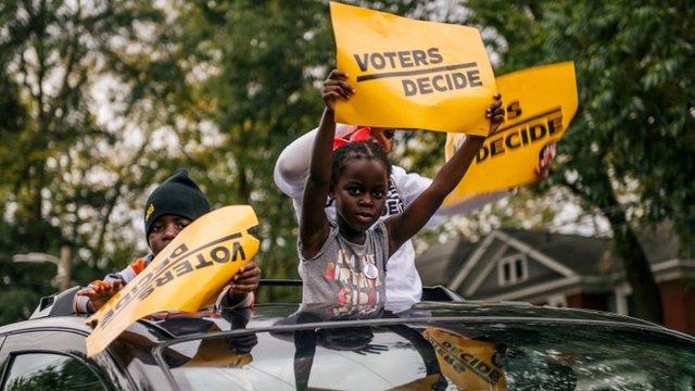 """Menores con carteles que dicen """"los votantes deciden"""""""
