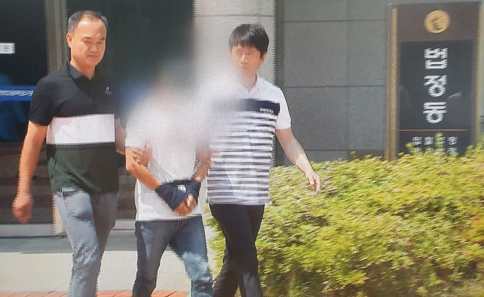 A man accused of beating his wife attends a local court in the southern city of Mokpo, South Korea