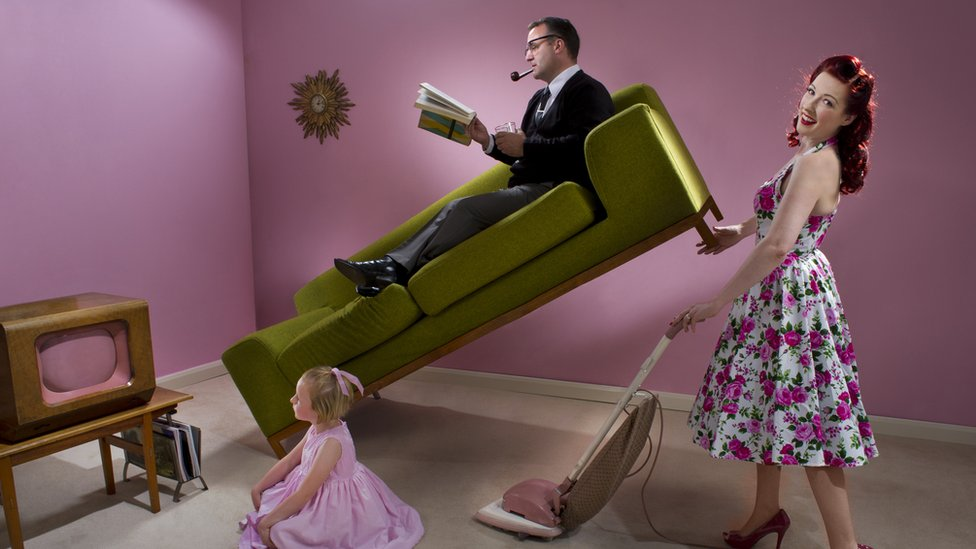 1950s stereotypical housewife uses vacuum cleaner while holding up her husband who's lying on sofa