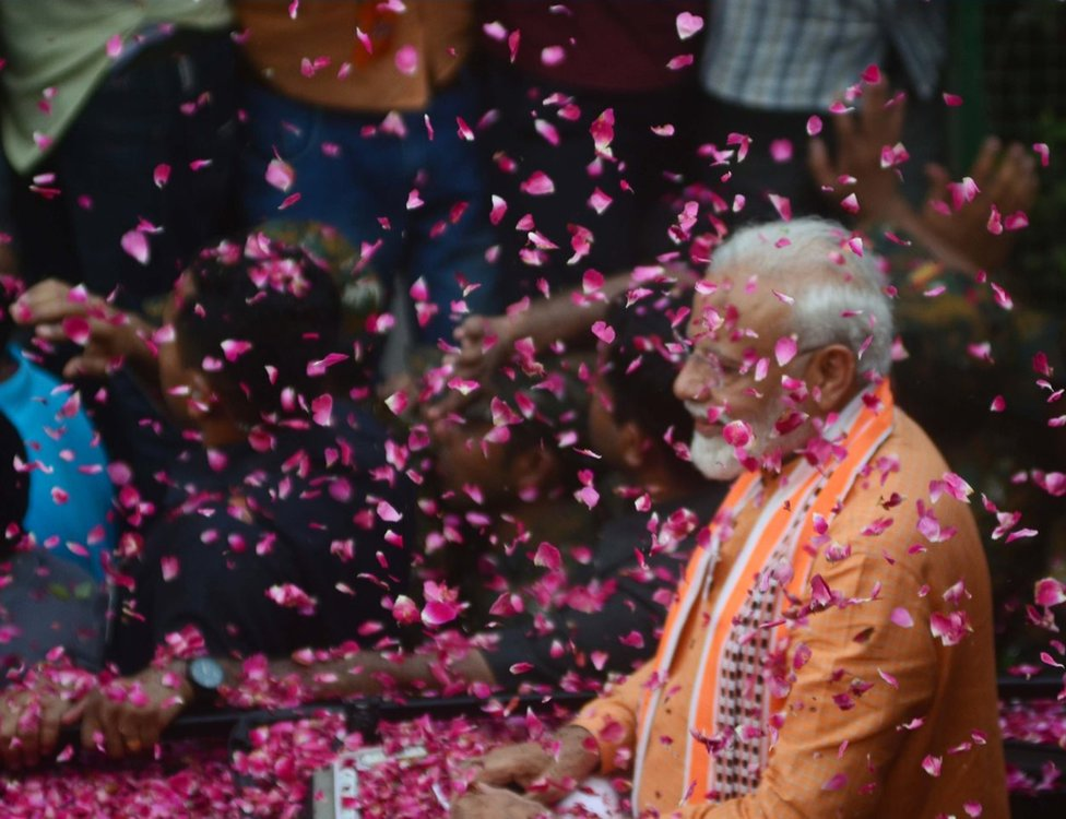 Indian Prime Minister Narendra Modi waves towards supporters during his road show in Varanasi on April 25, 2019 . PM Modi is visiting his parliamentary constituency Varanasi on April 25 and 26 .