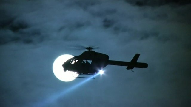 Helicopter silhouetted against Moon