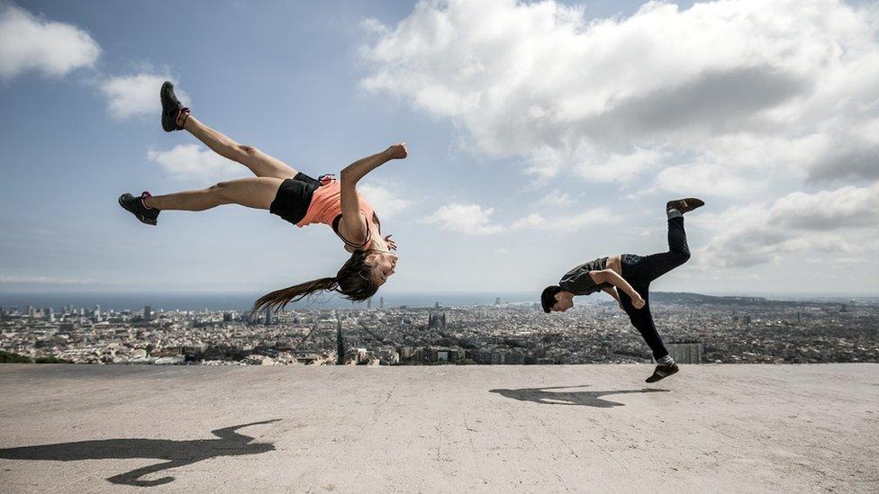 Un hombre y una mujer practican parkour en Barcelona.