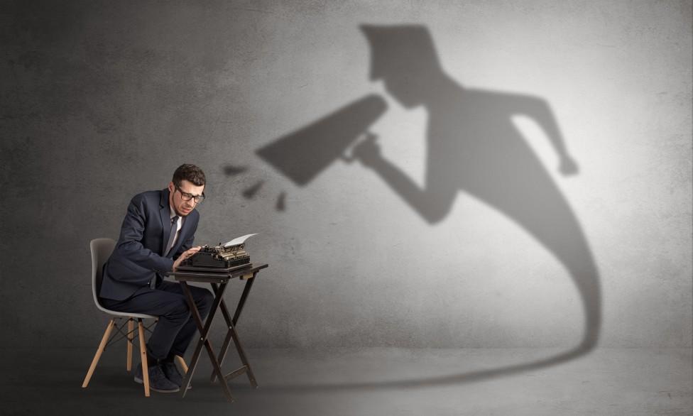 Un hombre con una máquina de escribir y una sombra de alguien gritando
