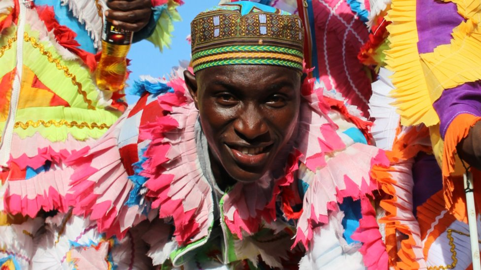 Man in hat and multi-coloured feather outfit in Sekondi Ghana