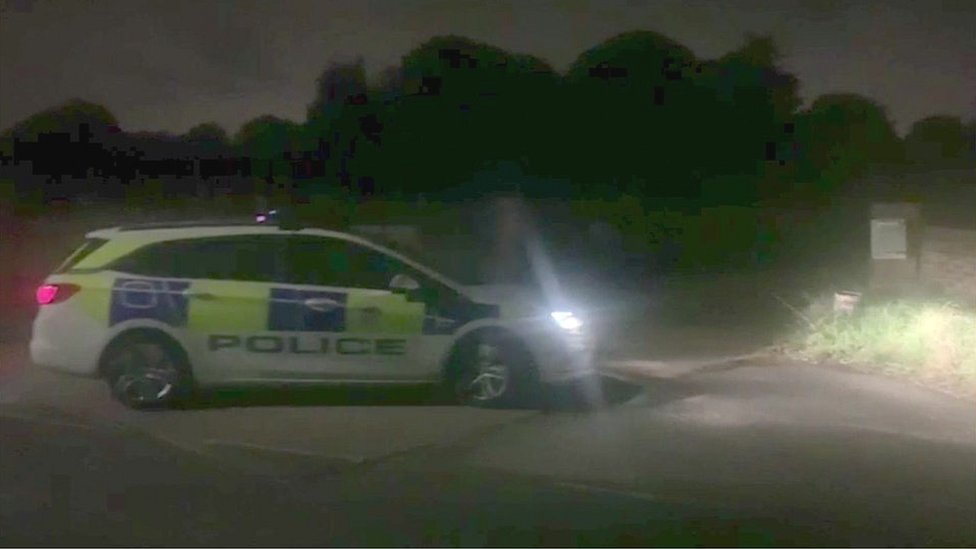 Marked police car outside a property on Park Road, Banstead