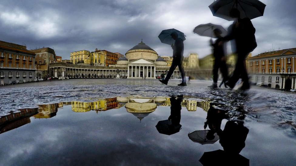 Pedestrians are reflected in a puddle as they protect themselves from the pouring rain with umbrellas while walking in downtown Naples, southern Italy