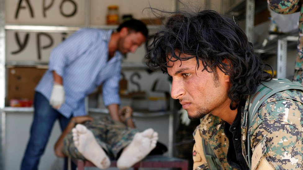 A Syrian Democratic Forces (SDF) fighter sit as medics treat his comrades injured by sniper fire by Islamic State militants in a field hospital in Raqqa, Syria, 28 June