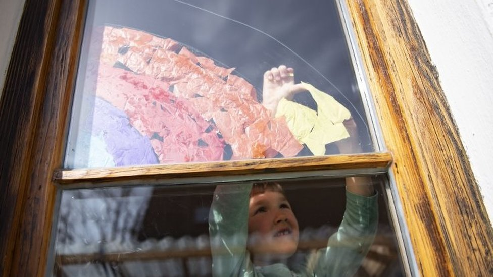 A five-year-old girl sticks a rainbow made of colourful pieces of paper to a window in Munich, Bavaria
