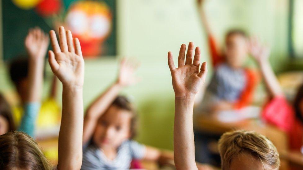 Niños levantando la mano en clase.