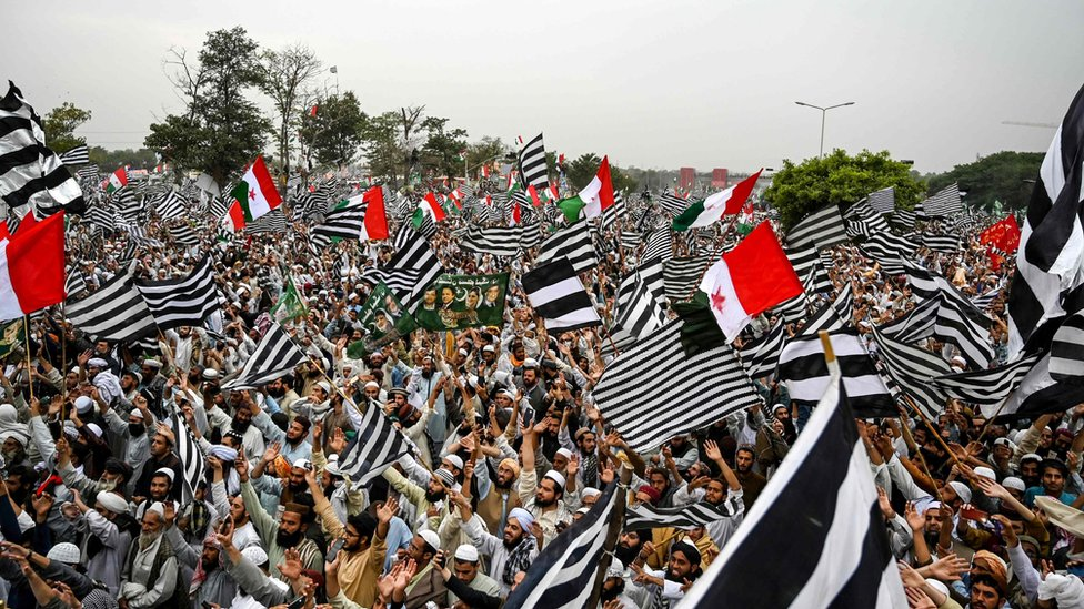 """Supporters of Islamic political party Jamiat Ulema-e-Islam (JUI-F) wave flags during an anti-government """"Azadi (Freedom) March"""" in Islamabad on November 1, 2019"""