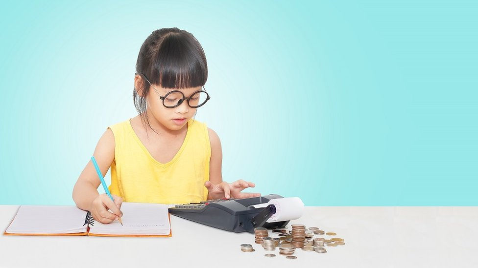 Little girl using a calculator and notepad with cash
