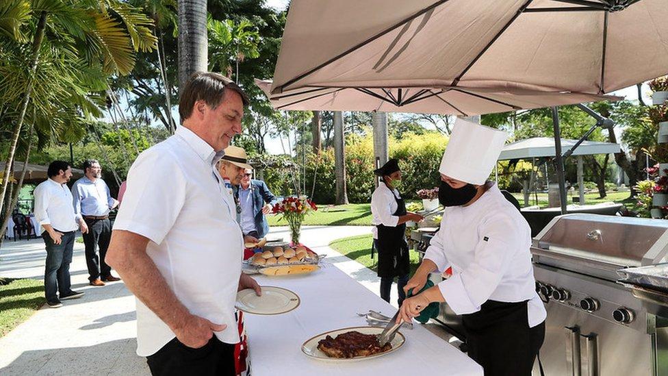 Bolsonaro em frente a mesa em que churrasqueira serve carne, em área aberta e arborizada