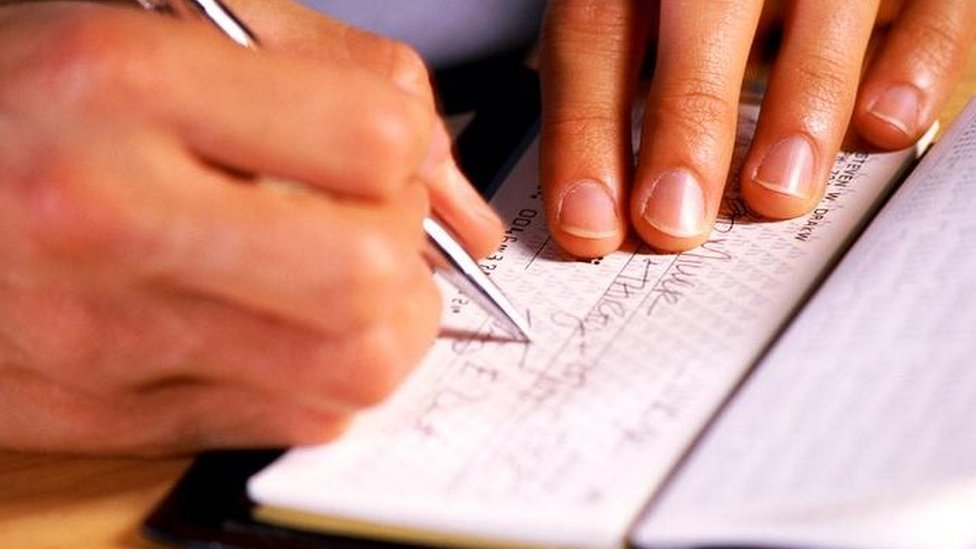 Hombre firmando un cheque.