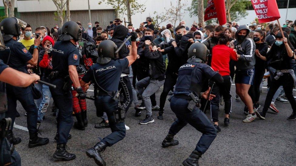 Police officers confront protesters next to the South Station, in Madrid, during a protest against coronavirus restrictions
