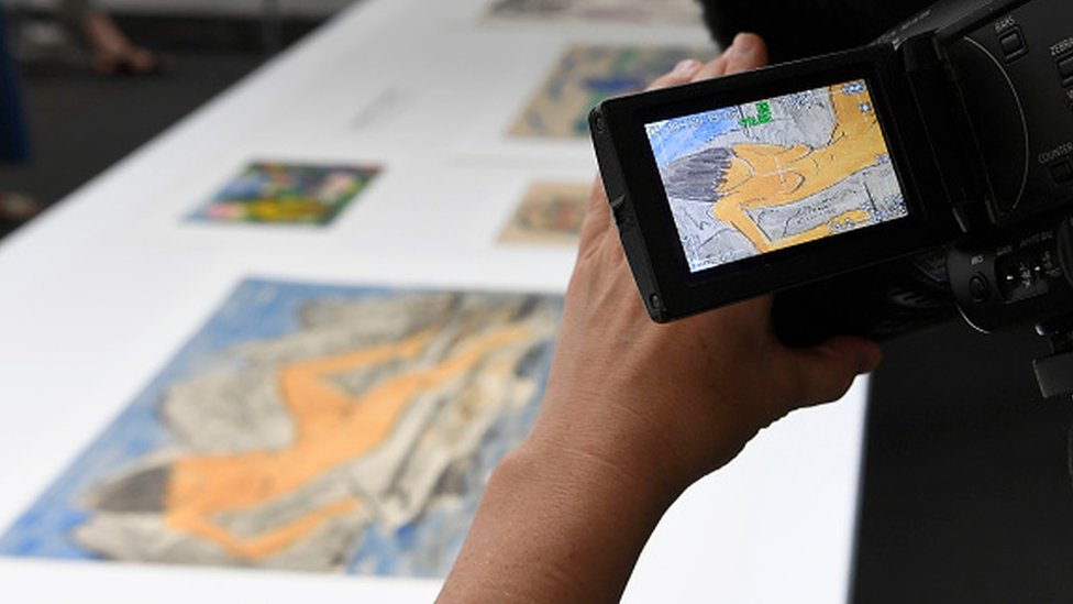 A journalist films the 'Liegende weiblicher Akt am Wasser' an aquarelle by German expressionist Otto Mueller and coming from the estate of German collector Cornelius Gurlitt during a press preview of the first masterpieces of the estate of Gurlitt at the Museum of Fine Arts Bern (07 July 2017)