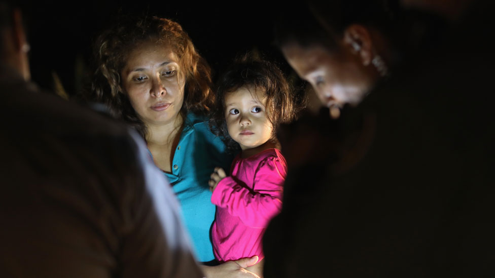 A two-year-old Honduran girl as her mother is searched and detained near the US-Mexico border on in McAllen, Texas, on 12 June 2018