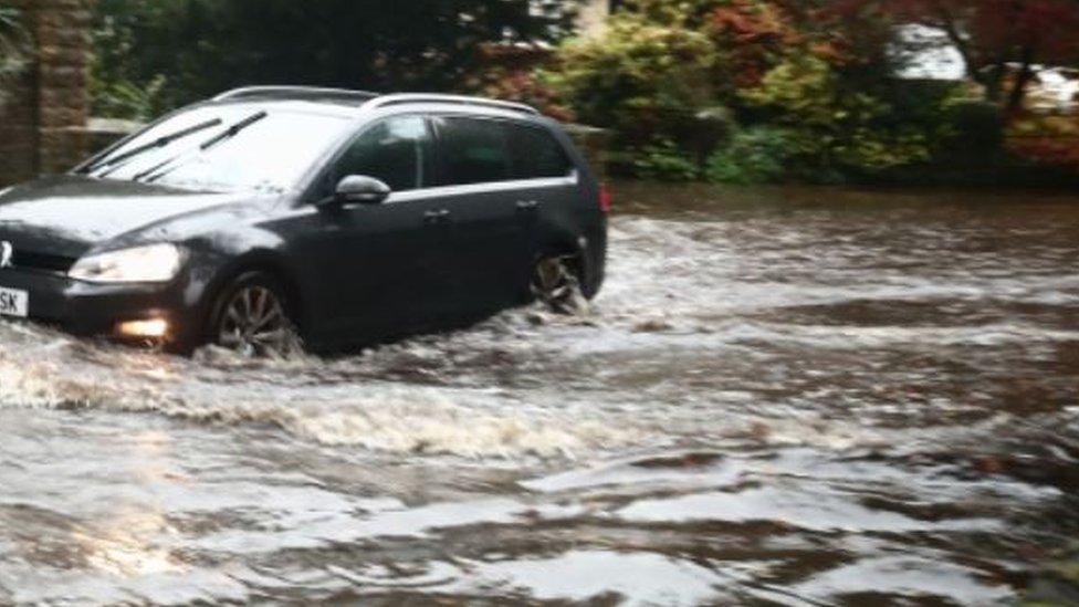 A car ploughs through flood water in Sheffield