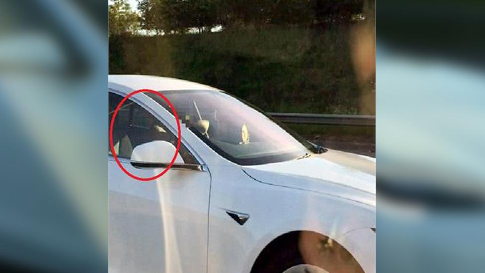Driver in passenger seat of Telsa