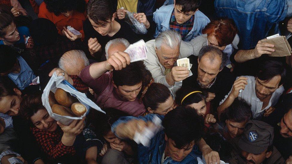 Gente luchando por coger comida durante el asedio a Sarajevo en la guerra de Bosnia.