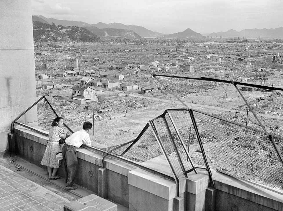 A couple stand on a damaged building and look out over the ruins of Hiroshima