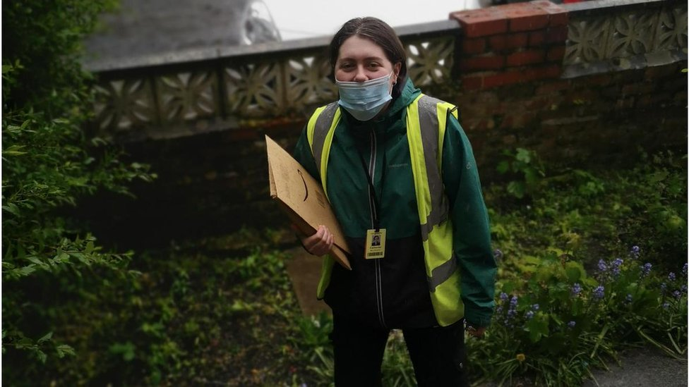 Cath is wearing a facemask as she delivers a parcel to someone's house