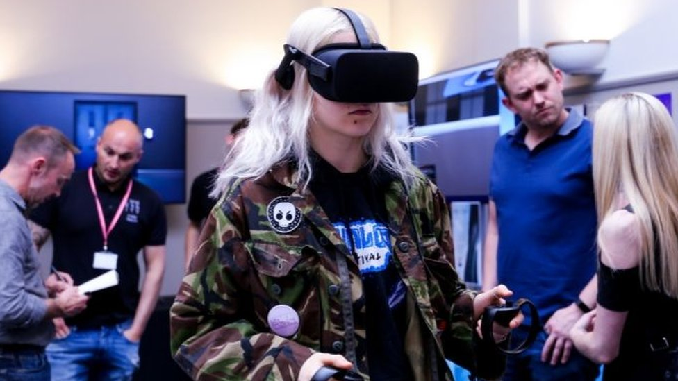 A conference attendee tries out an Oculus VR headset.