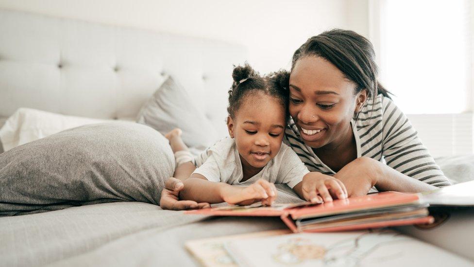 Madre e hija leyendo en la cama.