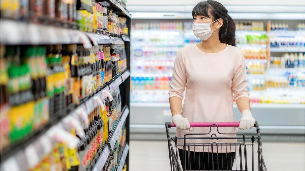 Mujer en supermercado con mascarilla.