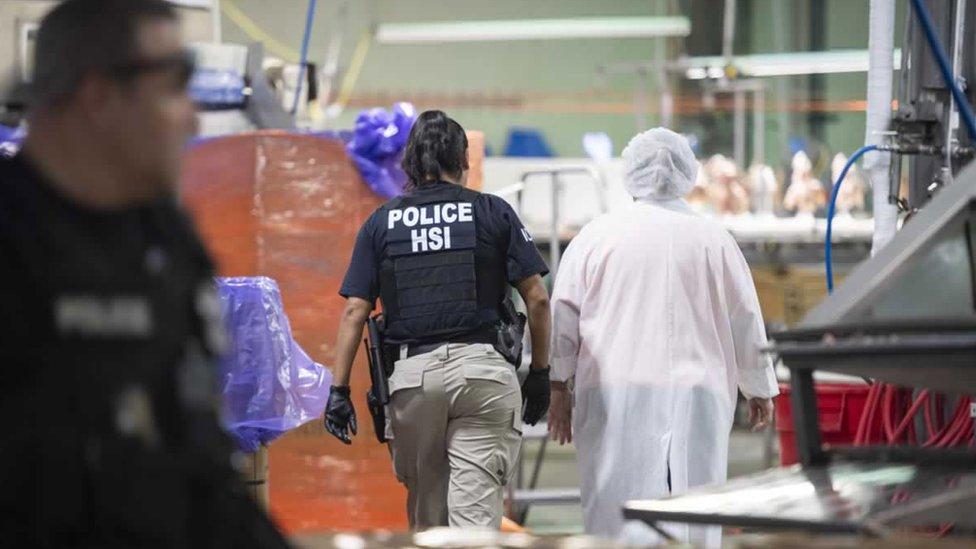 Una agente del Departamento de Investigaciones de Seguridad Nacional de Estados Unidos con una persona trabajadora de una planta procesadora en Misisipi