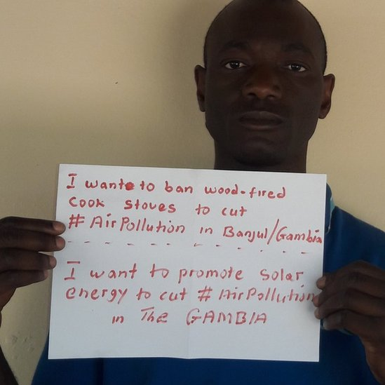 "Adboulie Sey holding a sign saying ""I want to ban wood fired cook stoves to cut #AirPollution in Banjul, Gambia. I want to promote solar energy to cut #AirPollution in the Gambia."""