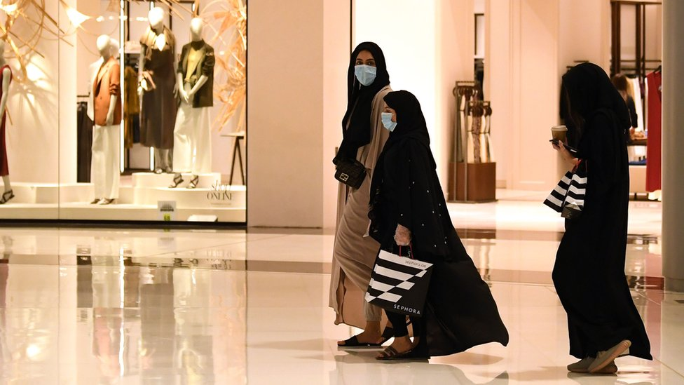 Women wearing face masks walk in the Mall of Dubai on 28 April 2020