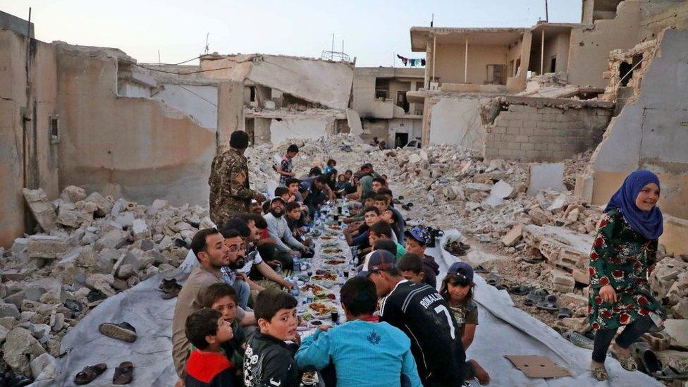 Un grupo de menores come en una zona de ruinas en Siria
