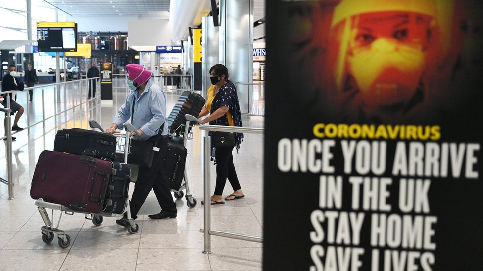 Passengers wear masks as they arrive at Heathrow Airport, in Britain