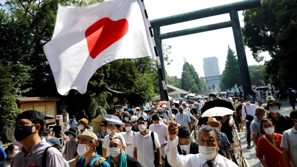 People walk through a Torii gate with a Japanese national flag as they visit Yasukuni Shrine