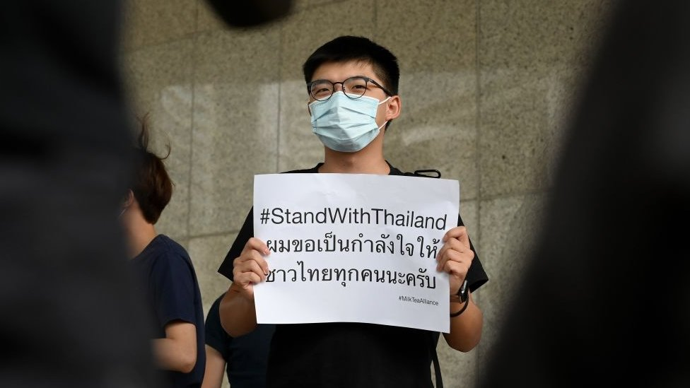 Pro-democracy activist Joshua Wong (C) holds a placard in solidarity with ongoing pro-democracy protests in Thailand