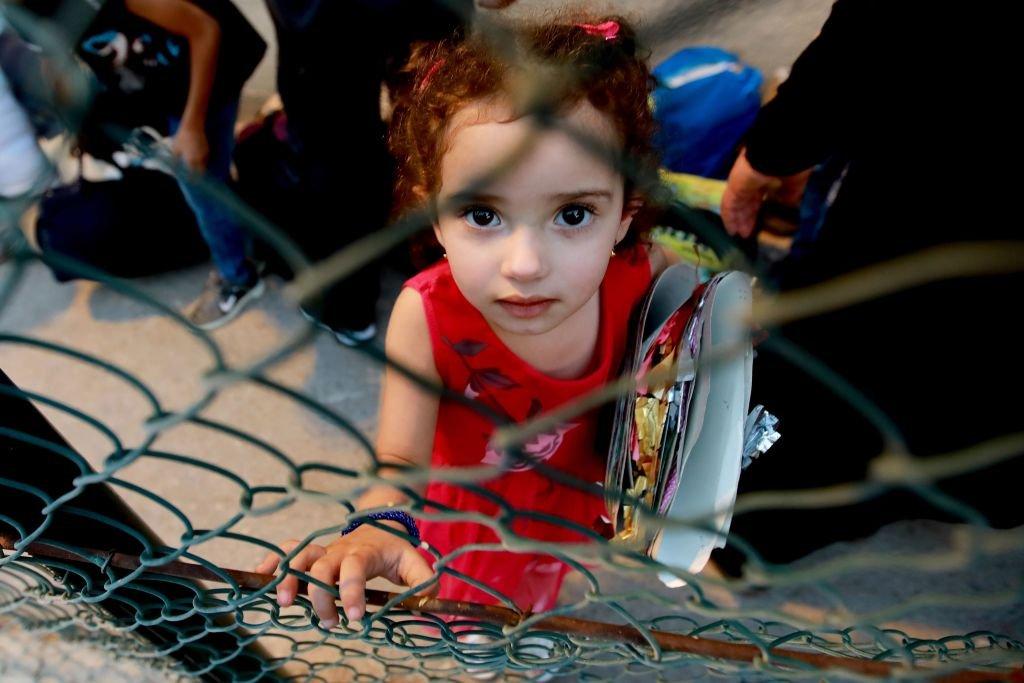 طفلة سورية لاجئة تنتظر بينما يستعد لاجئون لمغادرة العاصمة اللبنانية بيروت للعودة إلى ديارهم في سوريا في 9 سبتمبر 2018