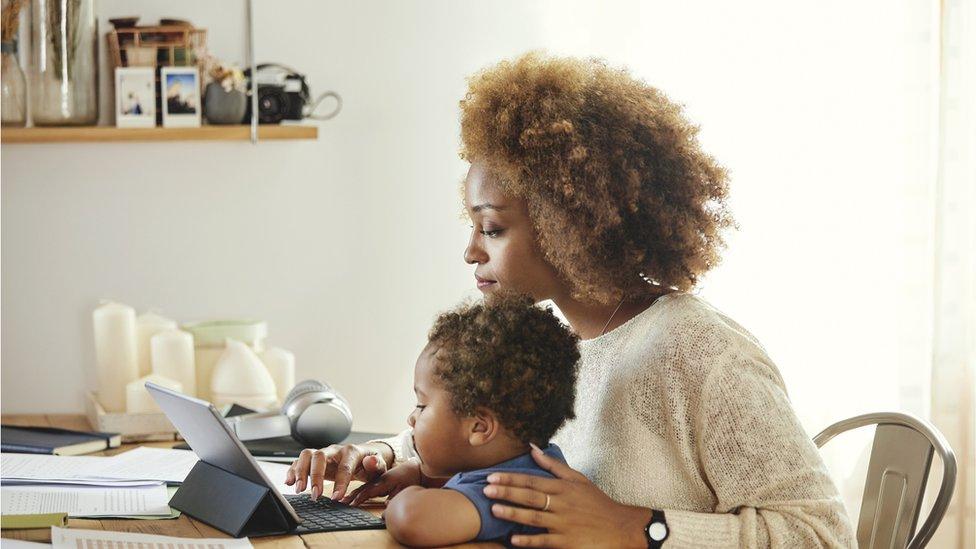 أم وطفلها أمام الكومبيوتر في المنزل