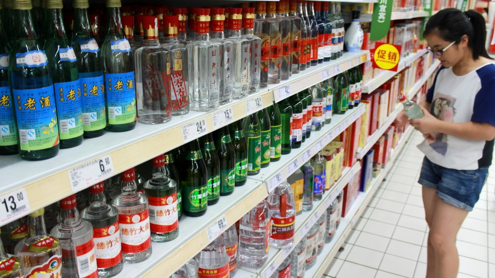 A woman holds a bottle of alcohol product at a supermarket in Nanjing, Jiangsu Province, China, August 6, 2016