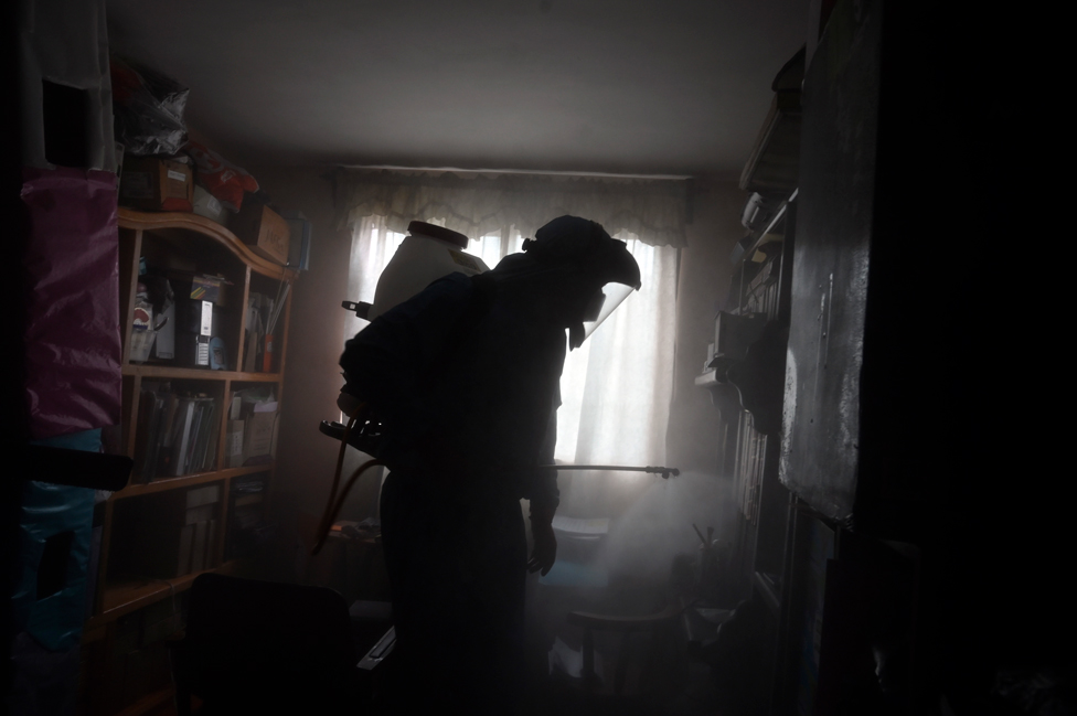 A local government worker disinfects a house in Mexico City, Mexico