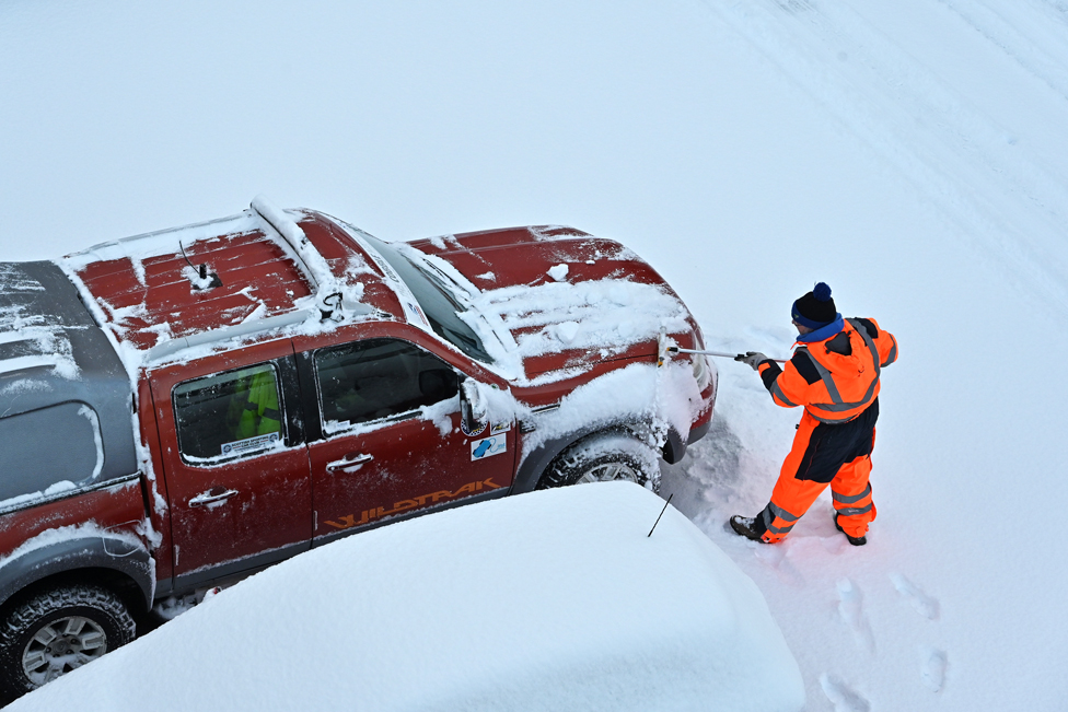 A man clears snow from his truck in a car park in Dalgety Bay, Fife, on 9 February 2021