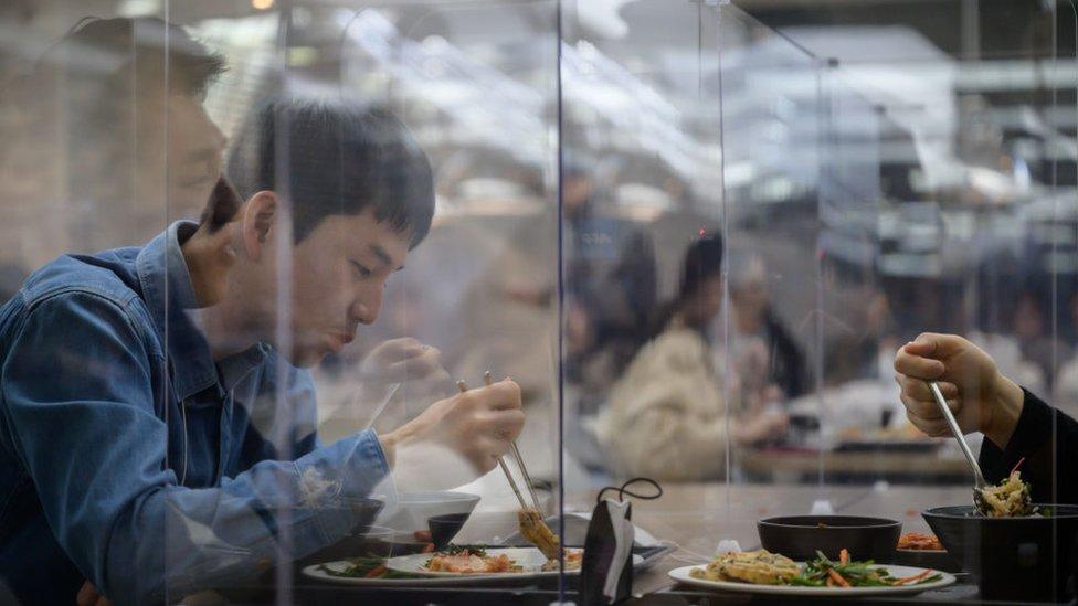 Trabajadores de Hyundai comiendo detrás de mamparas protectoras.
