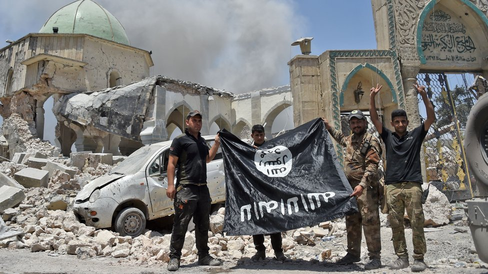 Soldados iraquíes sostienen una bandera de EI al revés, frente a las ruinas de una mezquita, junio de 2017